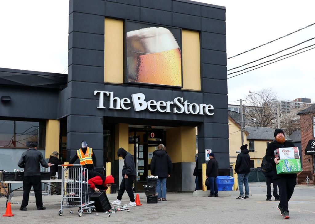 People line up in a parking lot for a long wait to return empties or buy beer at a Beer Store in downtown Toronto on April 16, 2020.