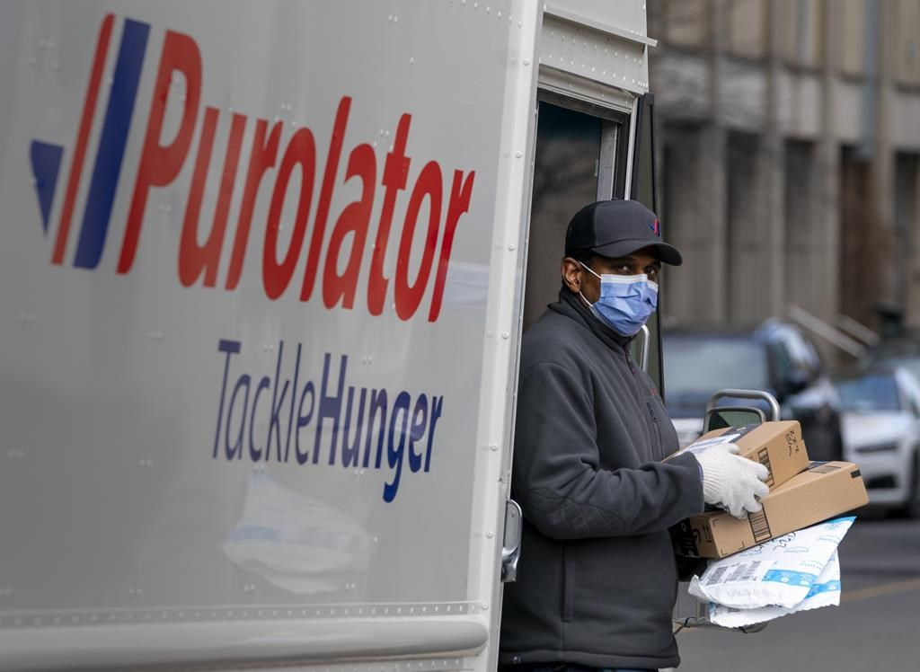A Purolator driver wears a mask as he makes deliveries in Toronto on March 24, 2020.