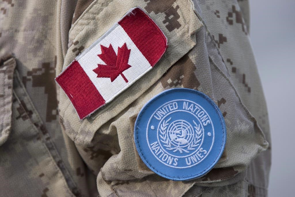 Canadian flag and the UN flag is shown on the sleeve of a Canadian soldier's uniform before boarding a plane at CFB Trenton in Trenton, Ont., on July 5, 2018.