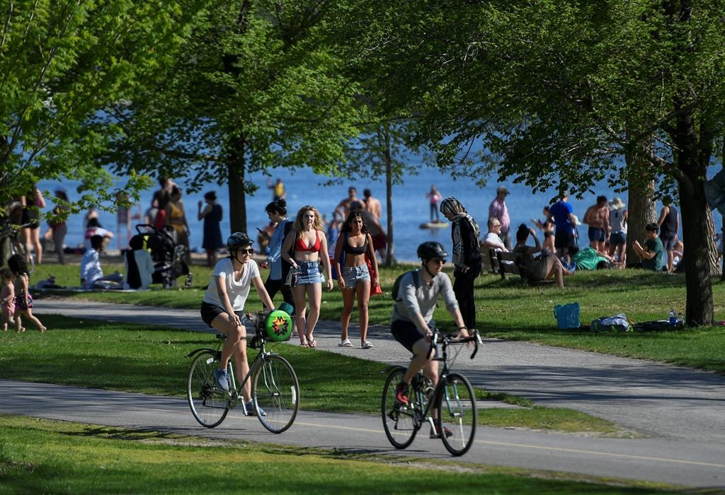 People enjoy the warm weather at Mooney's Bay Park in Ottawa, on Saturday, May 23, 2020, in the midst of the COVID-19 pandemic. THE CANADIAN PRESS/Justin Tang.