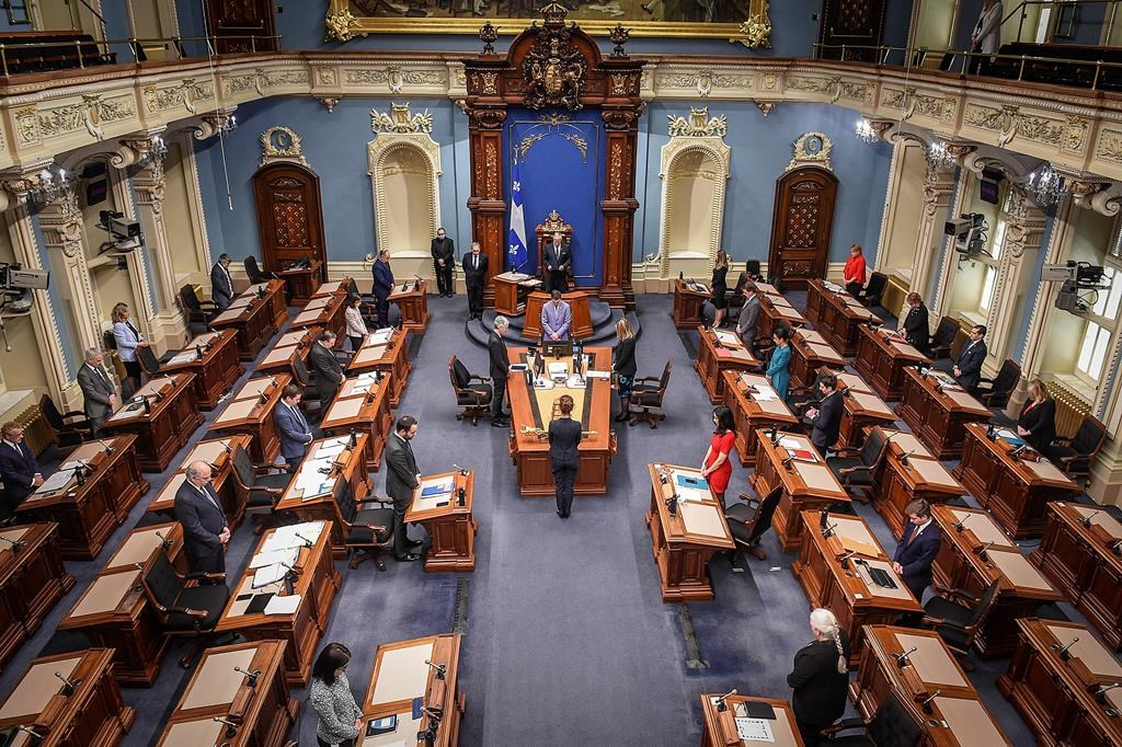 Members of the National Assembly stand in a minute of silence to honor the victims as the legislature resumes with limited attendance of members during the COVID-19 pandemic, Wednesday, May 13, 2020 at the legislature in Quebec City. THE CANADIAN PRESS/POOL Simon Clark.