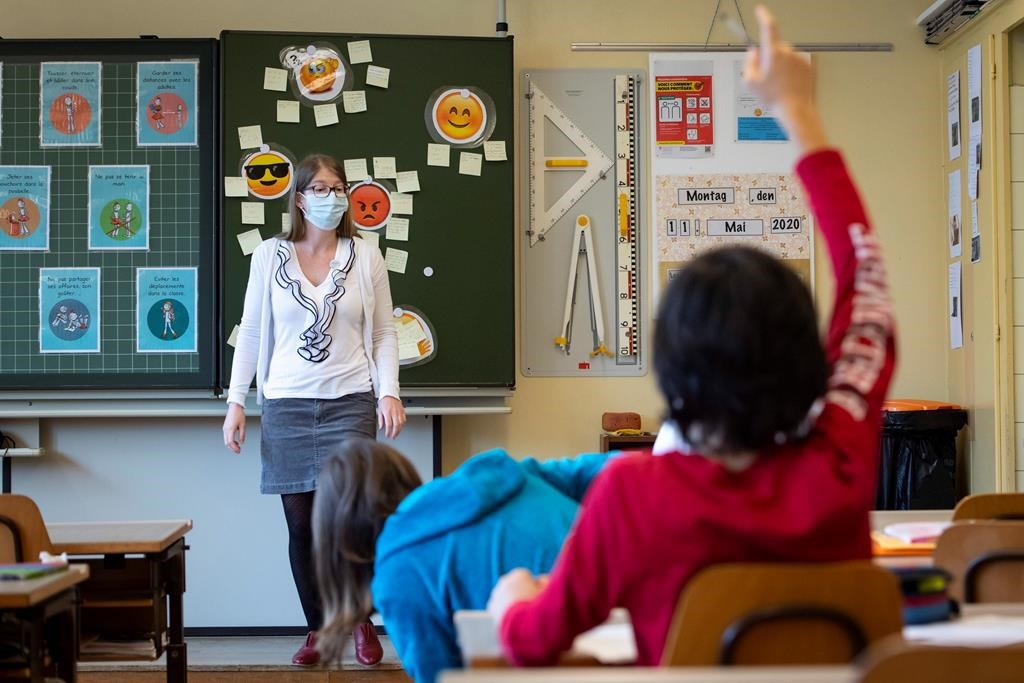 A teacher wearing protective face mask as she teaches close to pupils at a primary school in Morges, Switzerland, Monday, May 11, 2020.