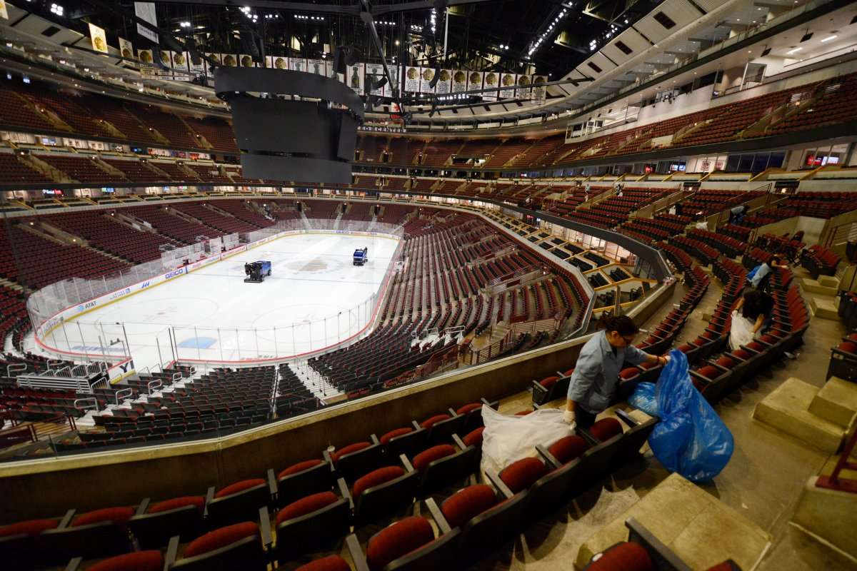 Workers clean up after an NHL hockey game between the Chicago Blackhawks and the San Jose Sharks at the United Center on Wednesday, March 11, 2020, in Chicago.