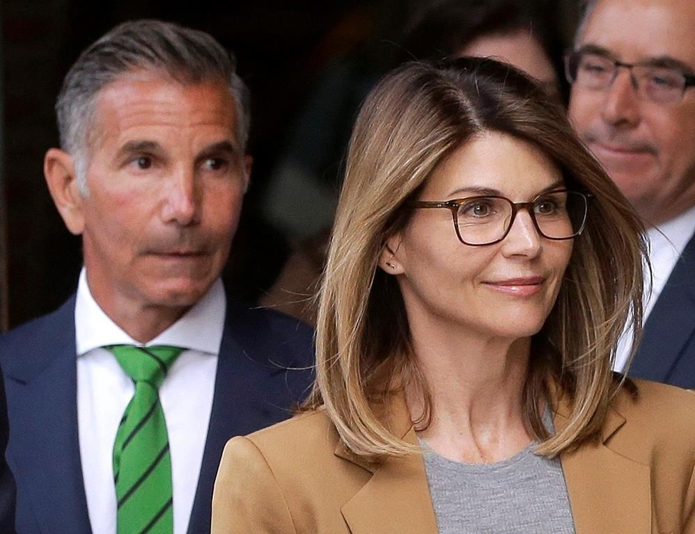 FILE - In this April 3, 2019, file photo, actress Lori Loughlin, front, and her husband, clothing designer Mossimo Giannulli, left, depart federal court in Boston.