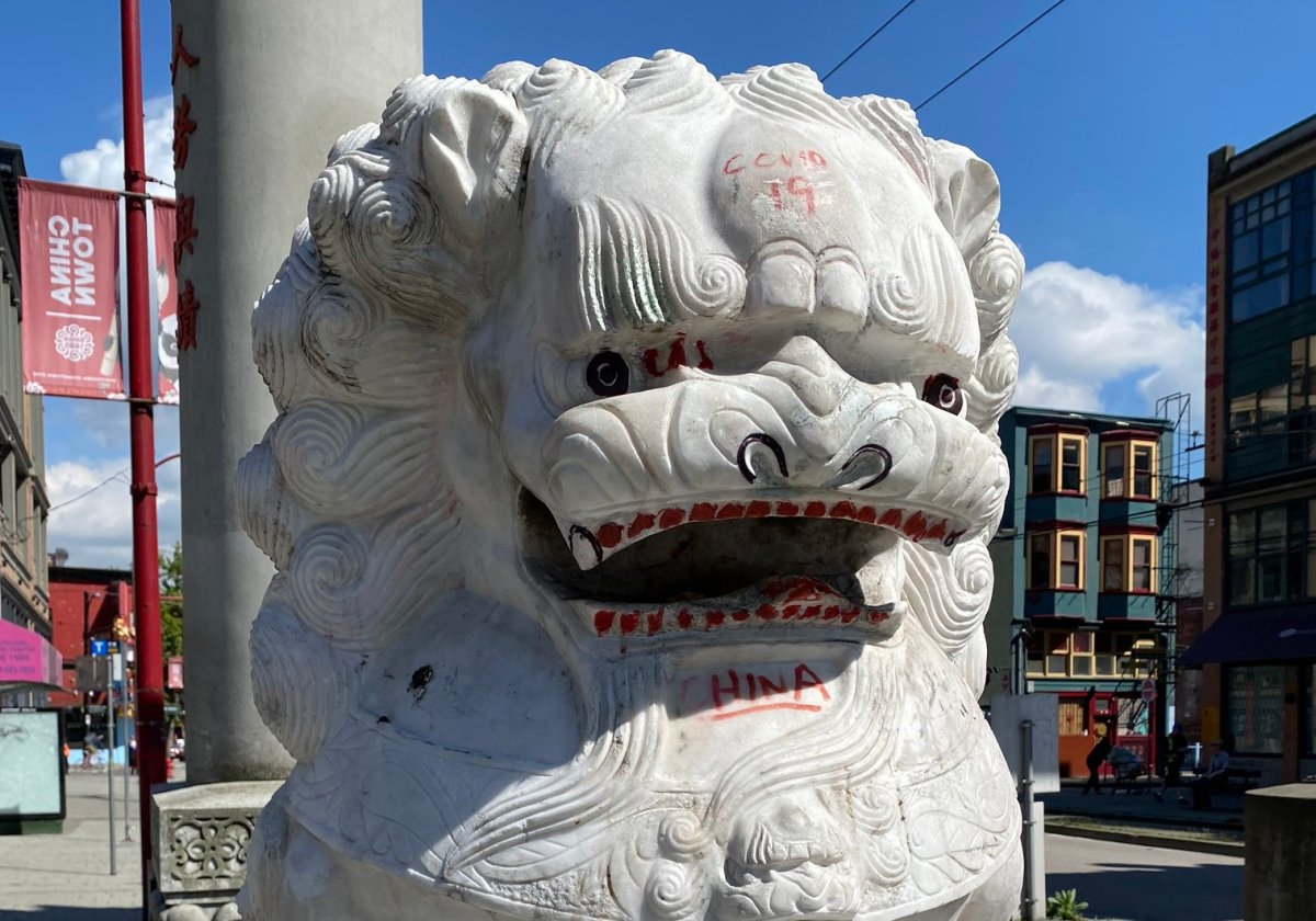 Racist graffiti seen on the lions at the base of the Millennium Gate in Vancouver's Chinatown.