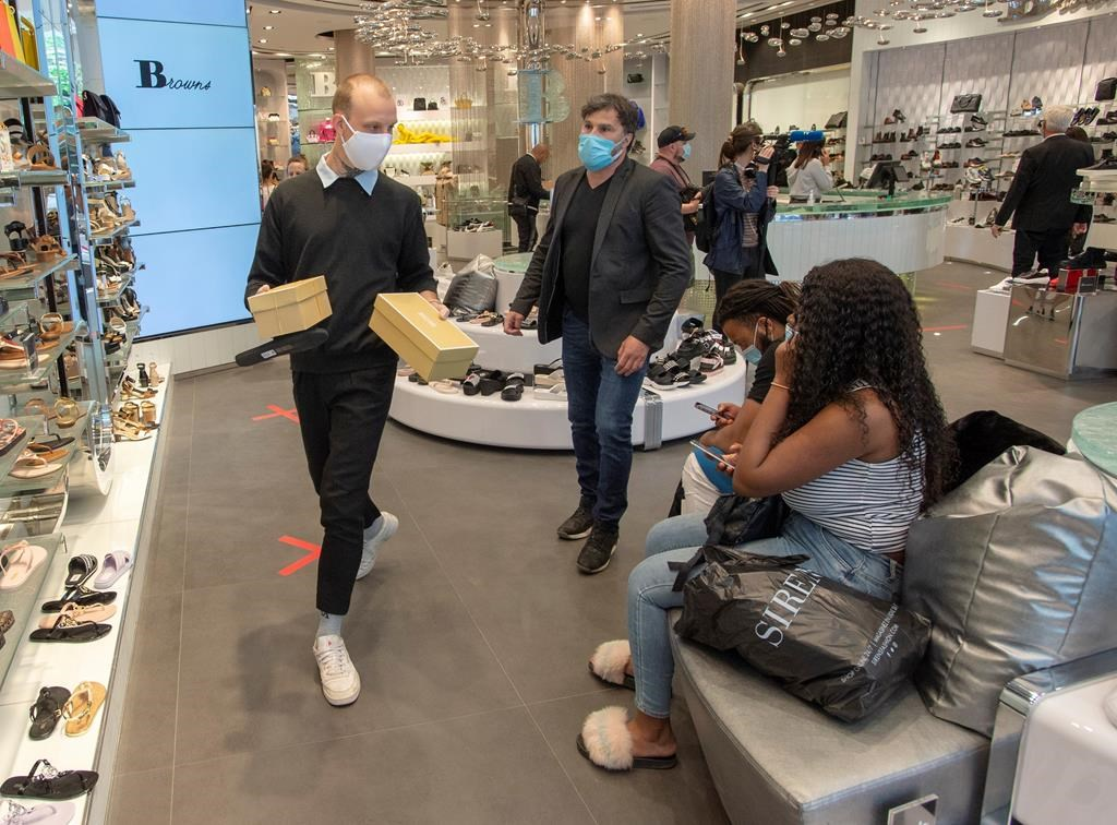 Customers shop for shoes at Brown's shoe store as many non-essential businesses are allowed to reopen Monday, May 25, 2020 in Montreal.