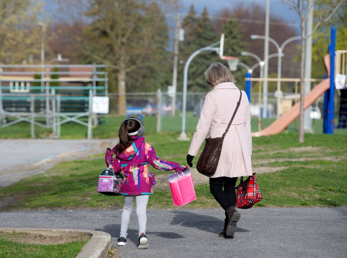 FILE PHOTO: A student is escorted into the schoolyard by a teacher as schools outside the greater Montreal region begin to reopen their doors amid the coronavirus disease (COVID-19) outbreak, in Saint-Jean-sur-Richelieu, Quebec, Canada May 11, 2020.