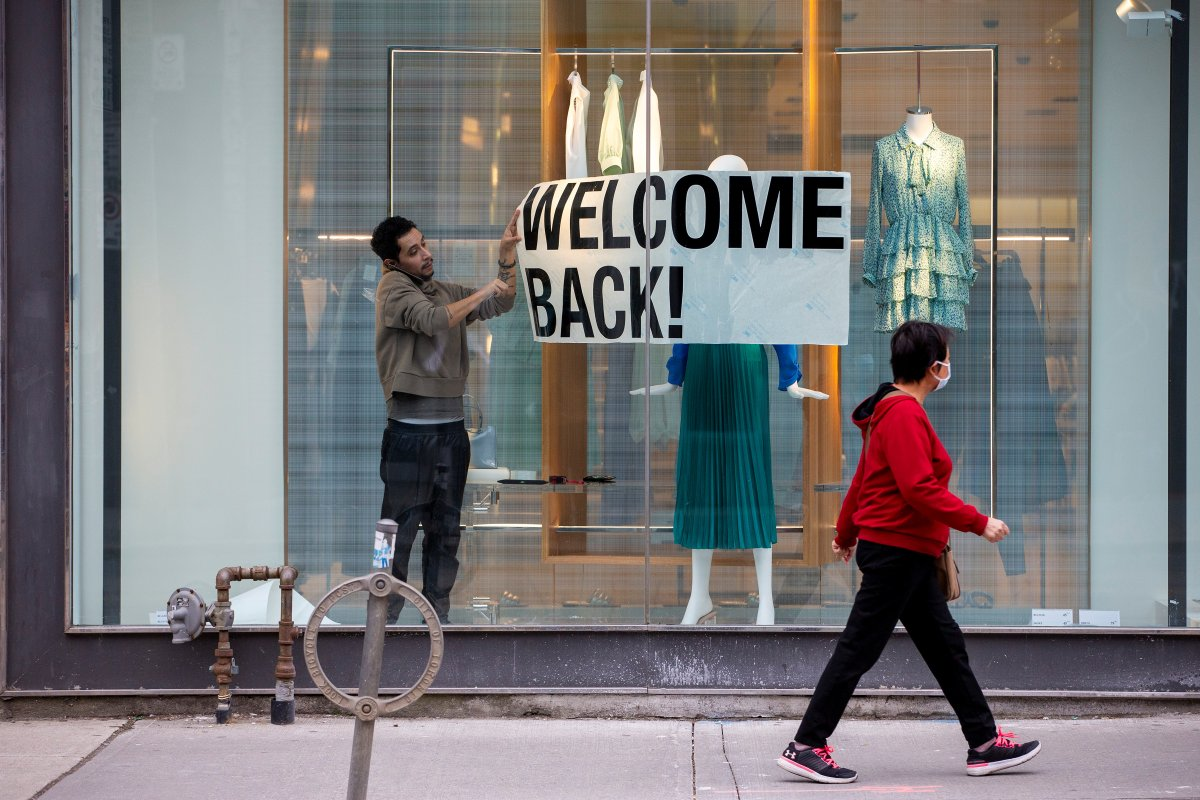 An employee at Zara puts up a sign during a phased reopening from COVID-19 restrictions in Toronto, May 19, 2020.