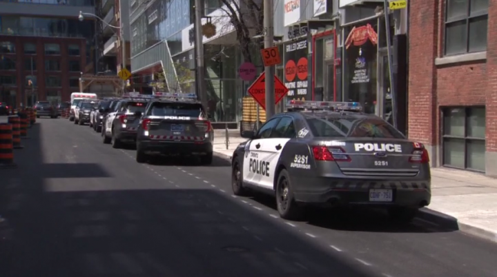 """Police at the scene where a man was found with """"significant injuries"""" in the area of Richmond and John streets on Saturday."""