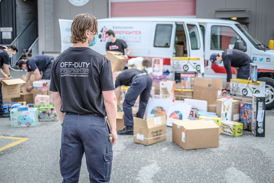 Vancouver firefighters load up donation Christmas toys they purchased in May to try and help struggling local businesses during the pandemic.