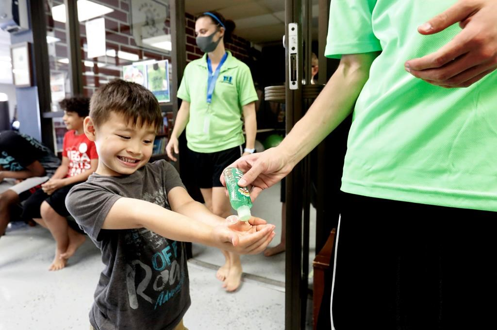 Bruce McCall, 5, smiles as he takes hand sanitizer during martial arts daycare summer camp at Legendary Blackbelt Academy in Richardson, Texas, Tuesday, May 19, 2020. As daycares and youth camps re-open in Texas, operators are following appropriate safety measure to insure kids stay safe from COVID-19. (AP Photo/LM Otero).