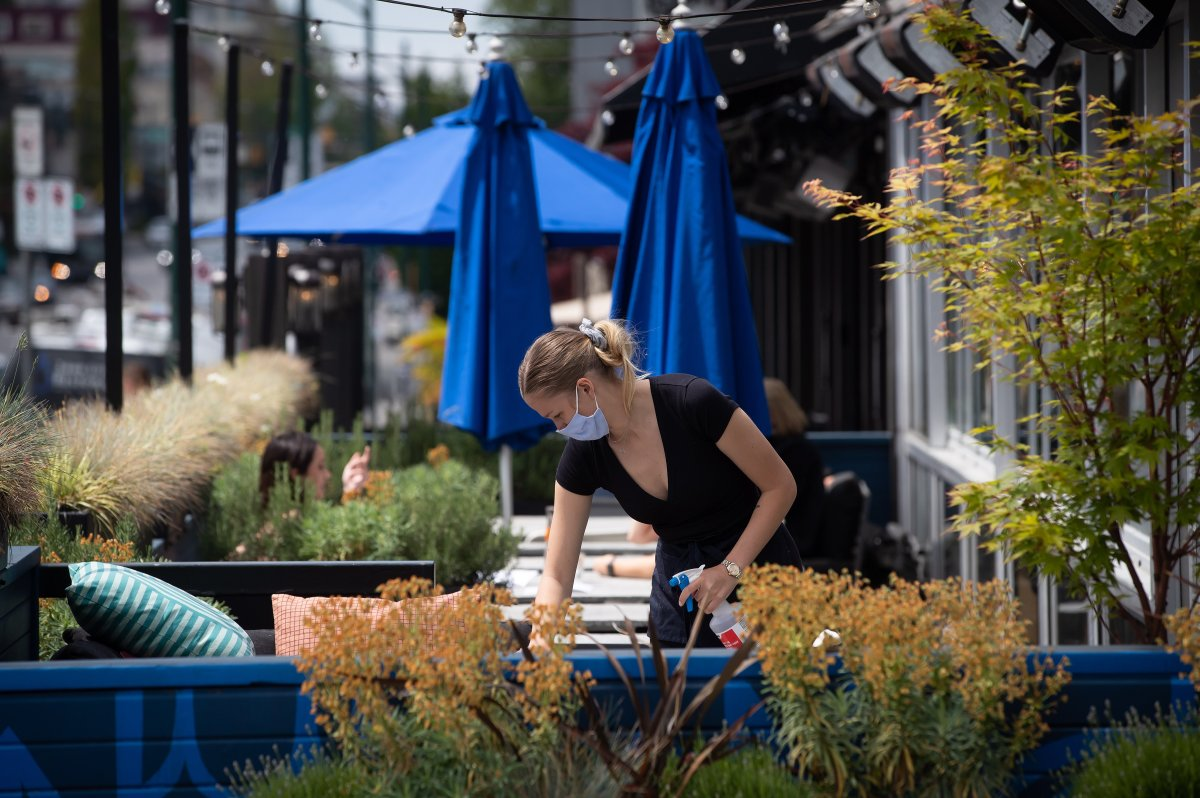 A server wears a face mask while cleaning a table on the patio at an Earls restaurant.