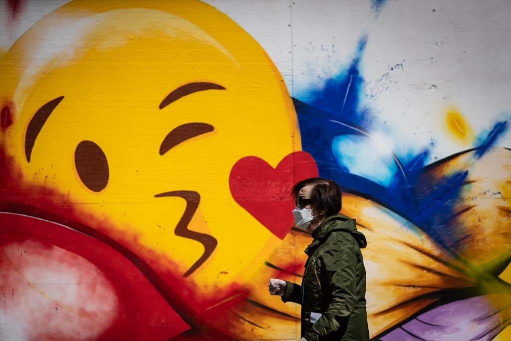 A woman wearing a protective face mask and gloves walks past a large emoji face painted on the boarded up windows of a store on Robson Street, in Vancouver, on Wednesday, May 6, 2020. British Columbia has outlined a gradual reopening of its economy with certain health services, retail outlets, restaurants, salons and museums resuming some operations in mid-May. THE CANADIAN PRESS/Darryl Dyck.