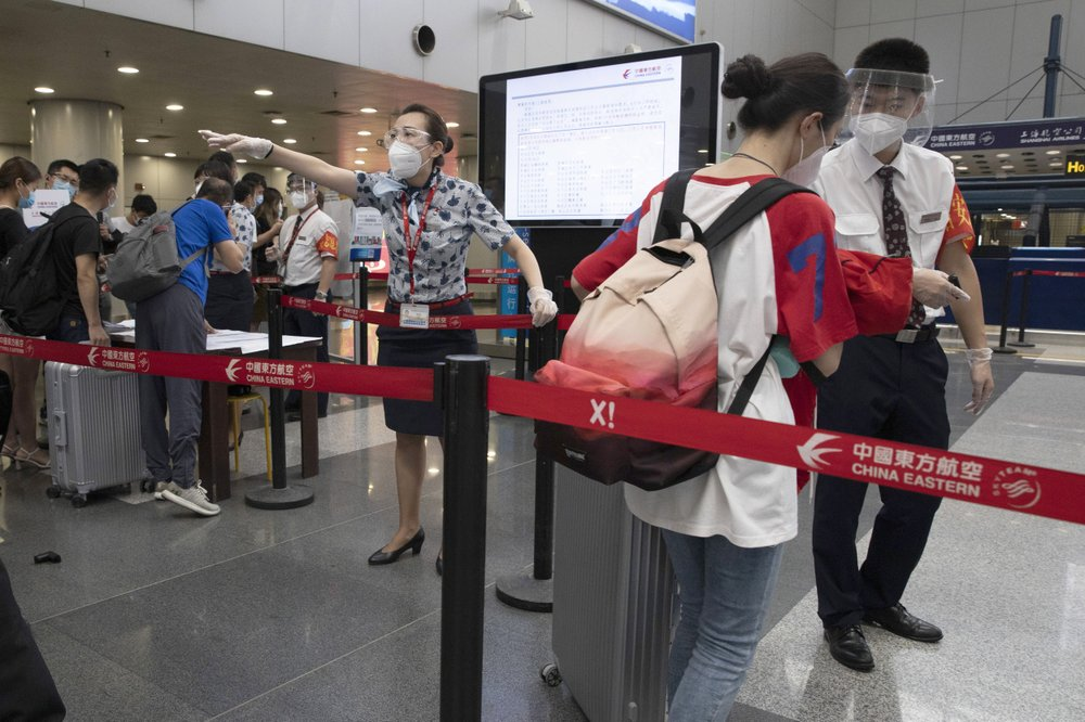 Airline employees redirect a traveller at a checkpoint for passengers from high risk areas to present their COVID-19 test results before checking in for their flight at the Beijing Capital Airport terminal 2 in Beijing on Wednesday, June 17, 2020. The Chinese capital on Wednesday canceled more than 60% of commercial flights and raised the alert level amid a new coronavirus outbreak, state-run media reported.