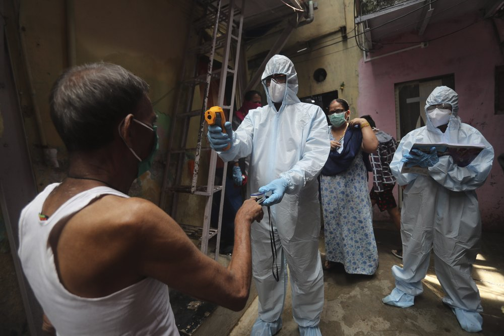 A doctor checks the temperature of a man during a free medical camp in Dharavi, one of Asia's largest slums in Mumbai, India, Saturday, June 20, 2020. India is the fourth hardest-hit country by the COVID-19 pandemic in the world after the U.S., Russia and Brazil.