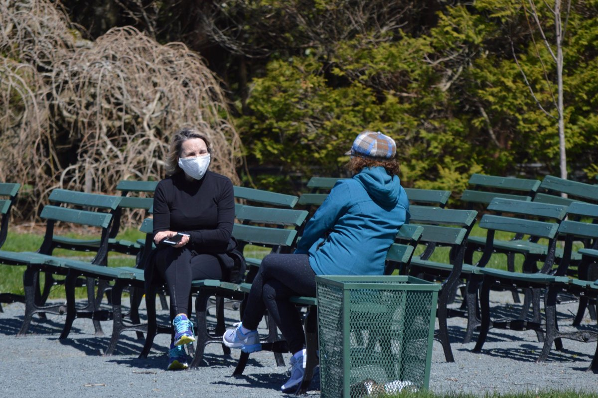 File - Two women, one of whom is wearing a mask, speak in the Halifax Public Gardens.