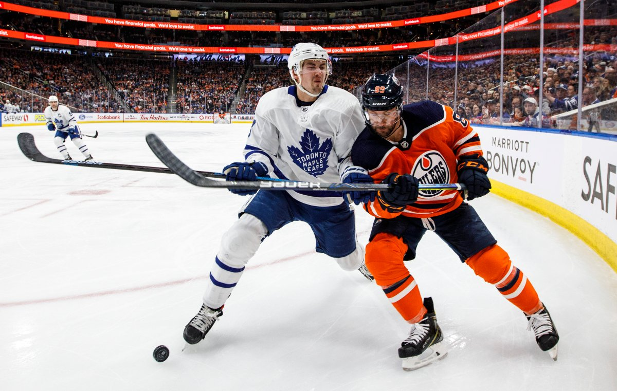 Toronto Maple Leafs' Justin Holl (3) and Edmonton Oilers' Sam Gagner (89) battle for the puck during second period NHL action in Edmonton, Alta., on Saturday December 14, 2019.