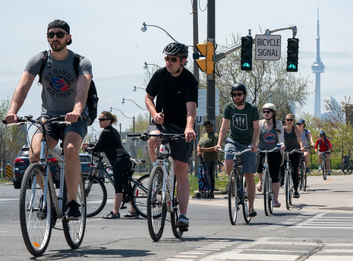 Cyclists negotiate a road crossing on a bike path in Toronto on Saturday, May 23, 2020.