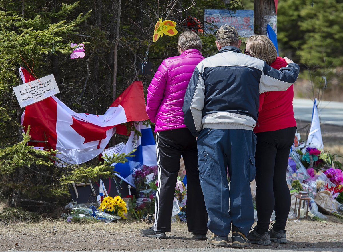 A family pays their respects to victims of the mass killings at a checkpoint on Portapique Road in Portapique, N.S. on Friday, April 24, 2020.