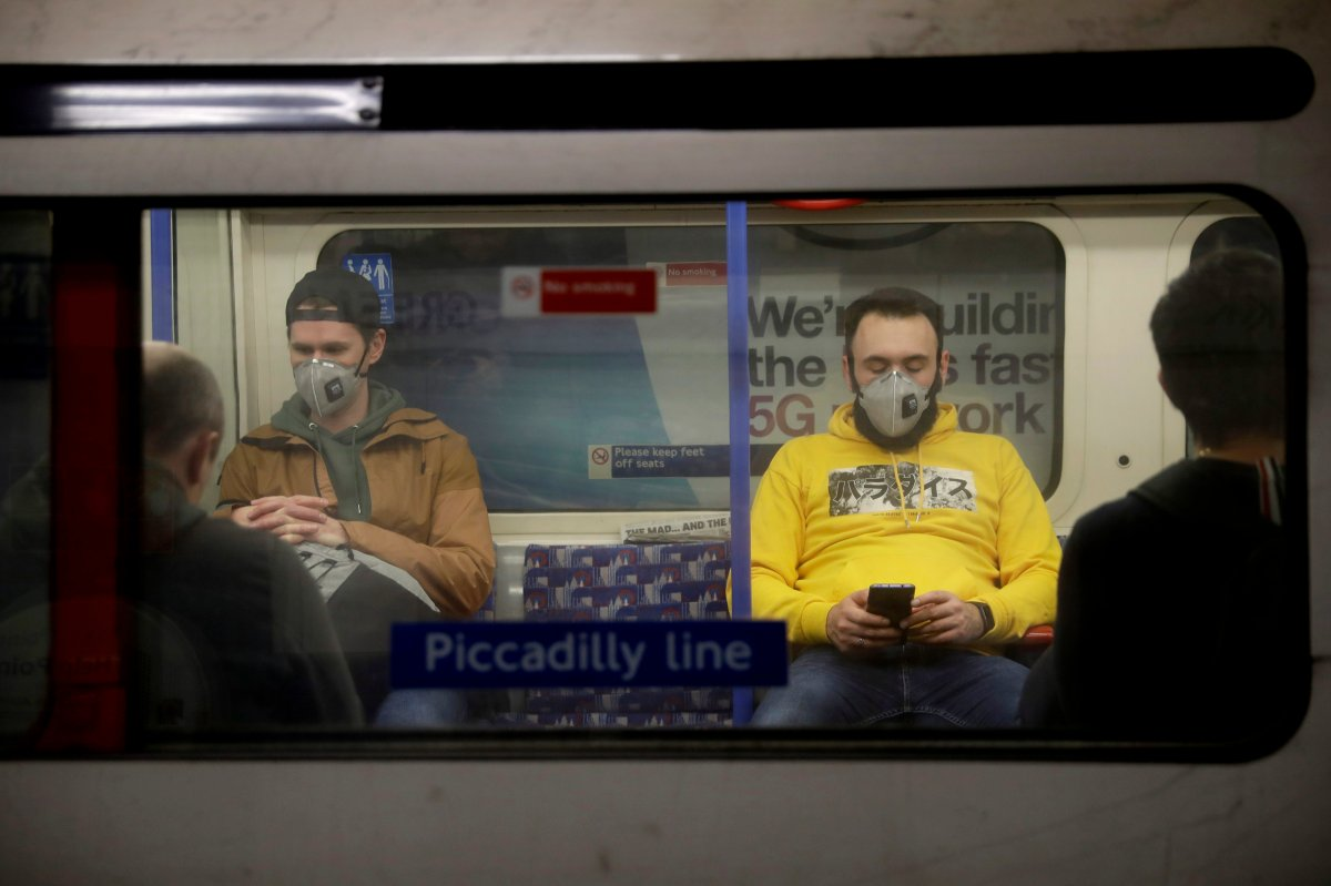 FILE - In this Friday, March 20, 2020 file photo, passengers wearing face masks travel on a Piccadilly Line underground train in London.