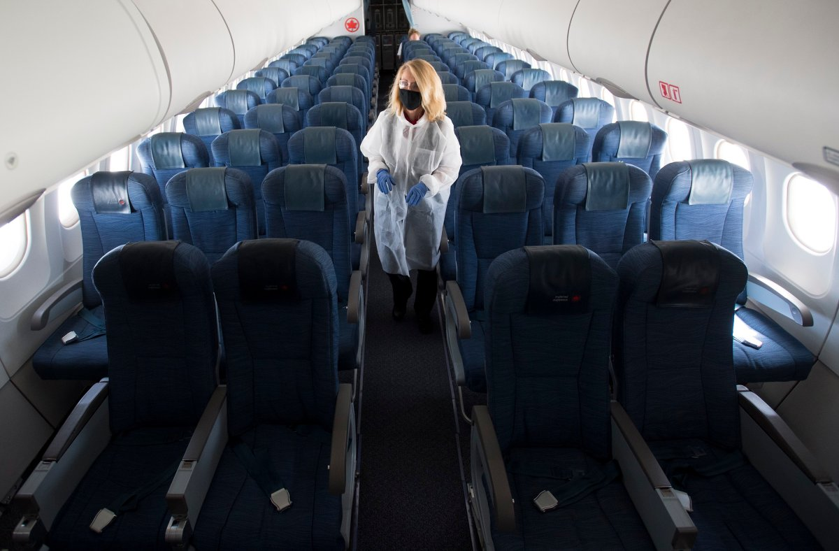 A flight attendant wears personal protective equipment as they walk through the back part of a near empty plane travelling from Calgary to Vancouver, Tuesday, June 9, 2020.