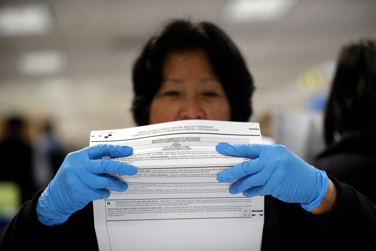 FILE - In this Nov. 4, 2016, file photo, a mail-in ballot is examined at the Santa Clara County Registrar of Voters in San Jose, Calif.