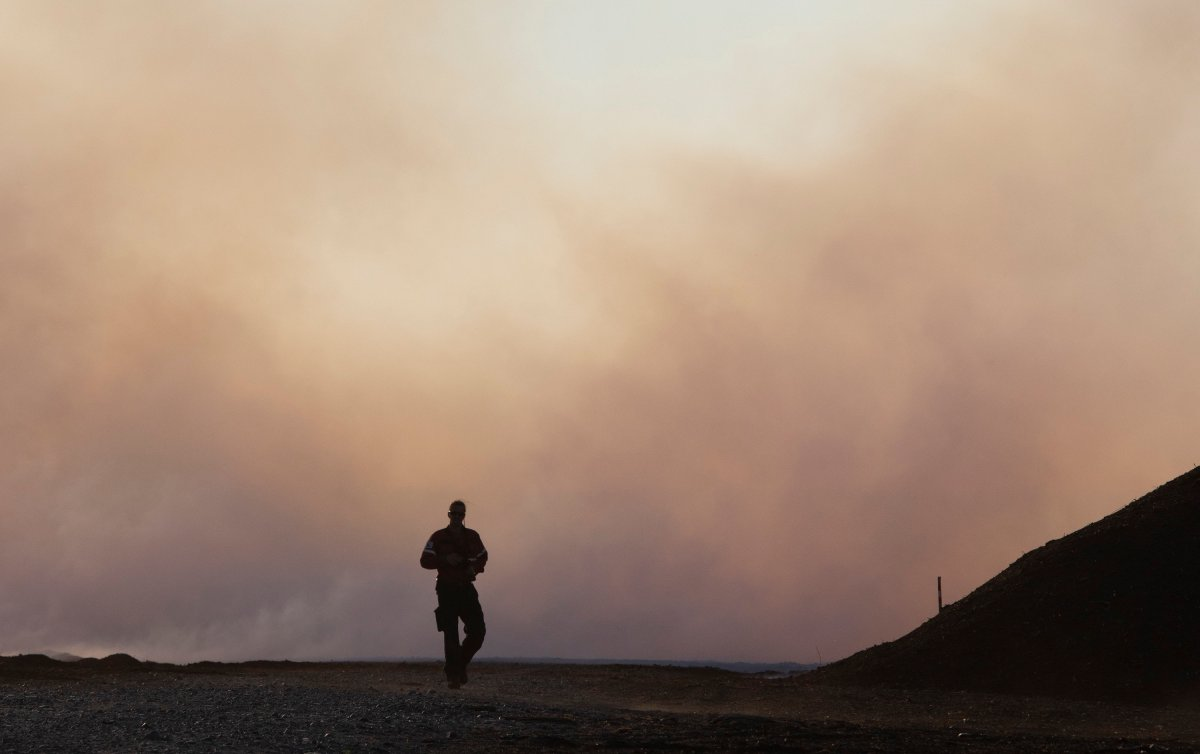 A firefighter walks toward a major field and forest fire at Lambert Peat moss fields in Riviere-Ouelle, Que., Friday, June 19, 2020. The fire spread over more than 10 km, pushed by strong winds.
