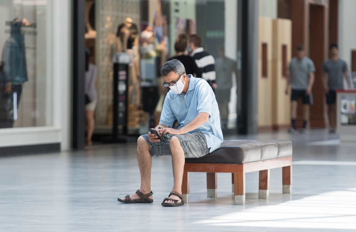 A man sits inside an open shopping mall in Montreal, Saturday, June 20, 2020, as the COVID-19 pandemic continues in Canada and around the world. THE CANADIAN PRESS/Graham Hughes.
