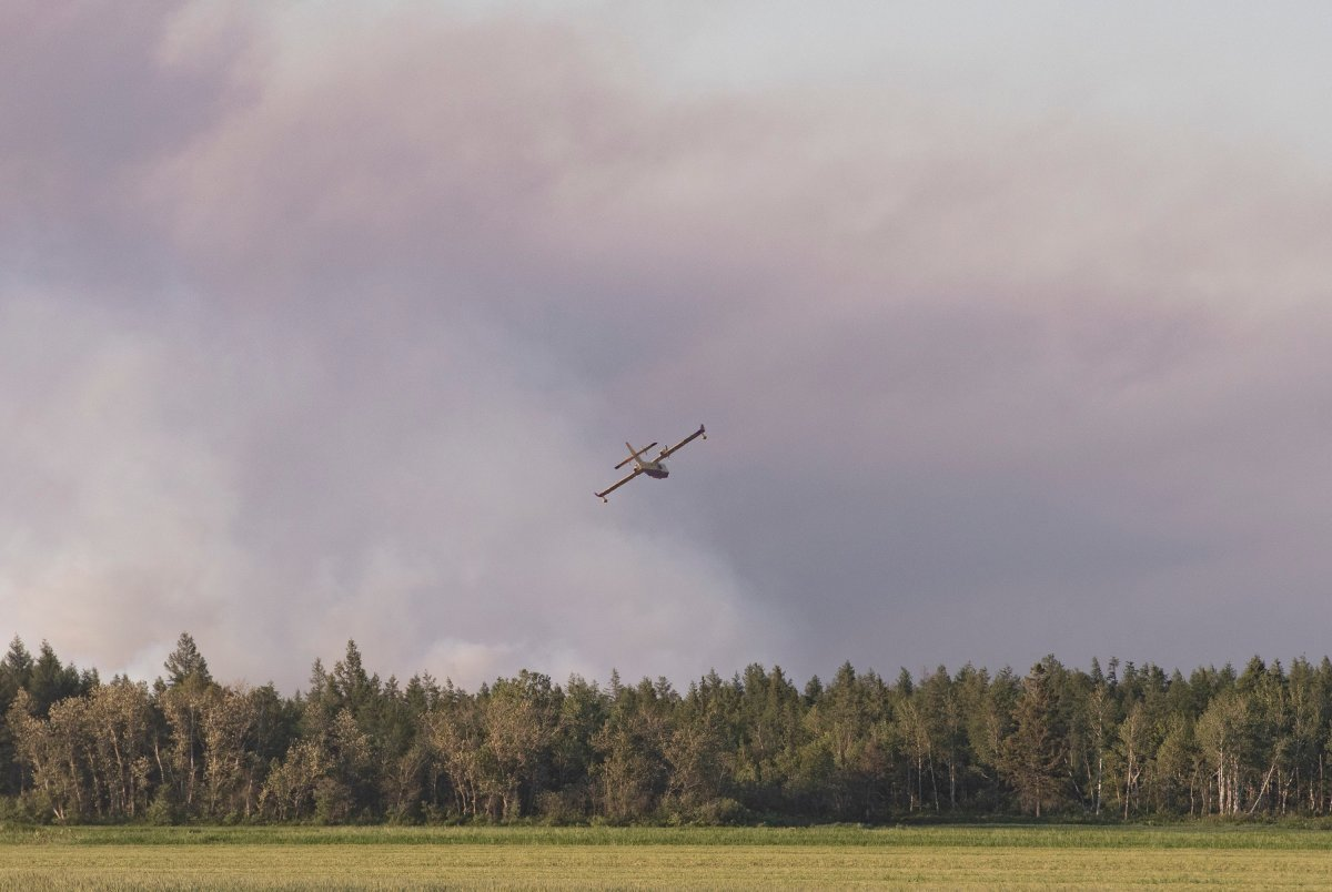 A water bomber flies toward a major field and forest fire at Lambert Peat moss fields in Riviere-Ouelle, Que., Friday, June 19, 2020. The fire spread over more than 10 kilometres, pushed by strong winds.