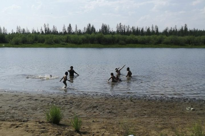 In this handout photo provided by Olga Burtseva, children play in the Krugloe lake outside Verkhoyansk, the Sakha Republic, about 4660 kilometers (2900 miles) northeast of Moscow, Russia, Sunday, June 21, 2020. A Siberian town that endures the world's widest temperature range has recorded a new high amid a hear wave that is contributing to severe forest fires. Russia's meteorological service said the thermometer hit 38 Celsius (100.4 F) on Saturday in Verkhoyansk, in the Sakha Republic about 4660 kilometers (2900 miles) northeast of Moscow.