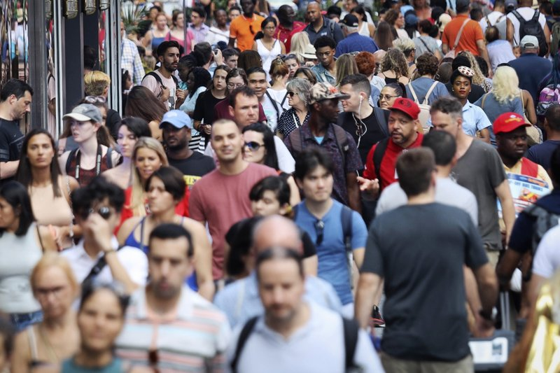 FILE - In this Aug. 22, 2019, file photo, people walk through New York's Times Square. The population of non-Hispanic whites in the U.S. has gotten smaller in the past decade as deaths have surpassed births in this aging demographic, and a majority of the population under age 16 is nonwhite for the first time though they are fewer in number than a decade ago, according to new figures released Thursday, June 25, 2020, by the U.S. Census Bureau.