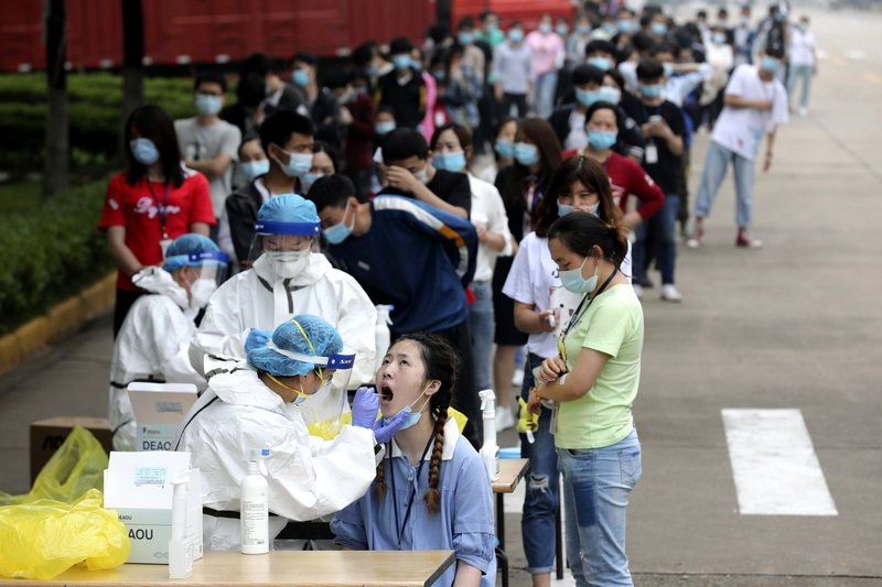 FILE - In this May 15, 2020 file photo, people line up for medical workers to take swabs for the coronavirus test at a large factory in Wuhan in central China's Hubei province. The Chinese city of Wuhan has tested nearly 10-million people for the new coronavirus in an unprecedented 19-day campaign to check an entire city.