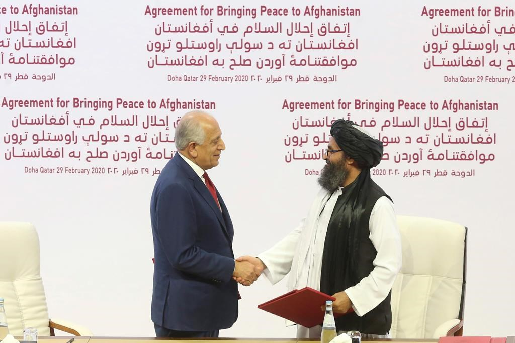 FILE - In this Feb. 29, 2020 file photo, U.S. peace envoy Zalmay Khalilzad, left, and Mullah Abdul Ghani Baradar, the Taliban group's top political leader shake hands after signing a peace agreement between Taliban and U.S. officials in Doha, Qatar.