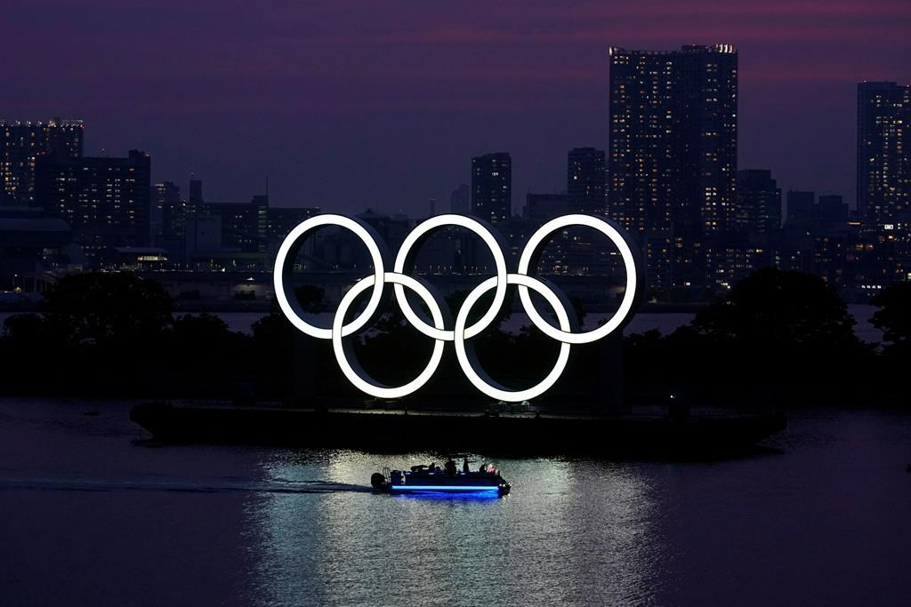 FILE - In this June 3, 2020, photo, the Olympic rings float in the water at sunset in the Odaiba section in Tokyo.