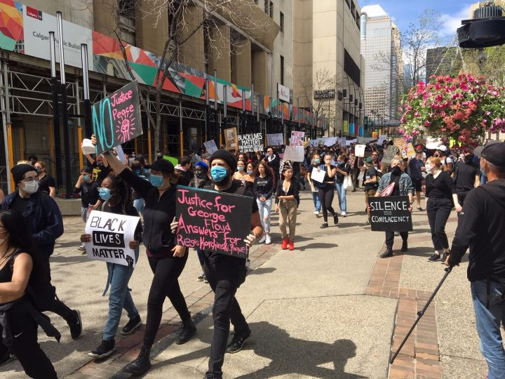 Residents walk the streets of downtown Calgary on Monday, June 1, 2020, as part of a protest following the death of George Floyd.
