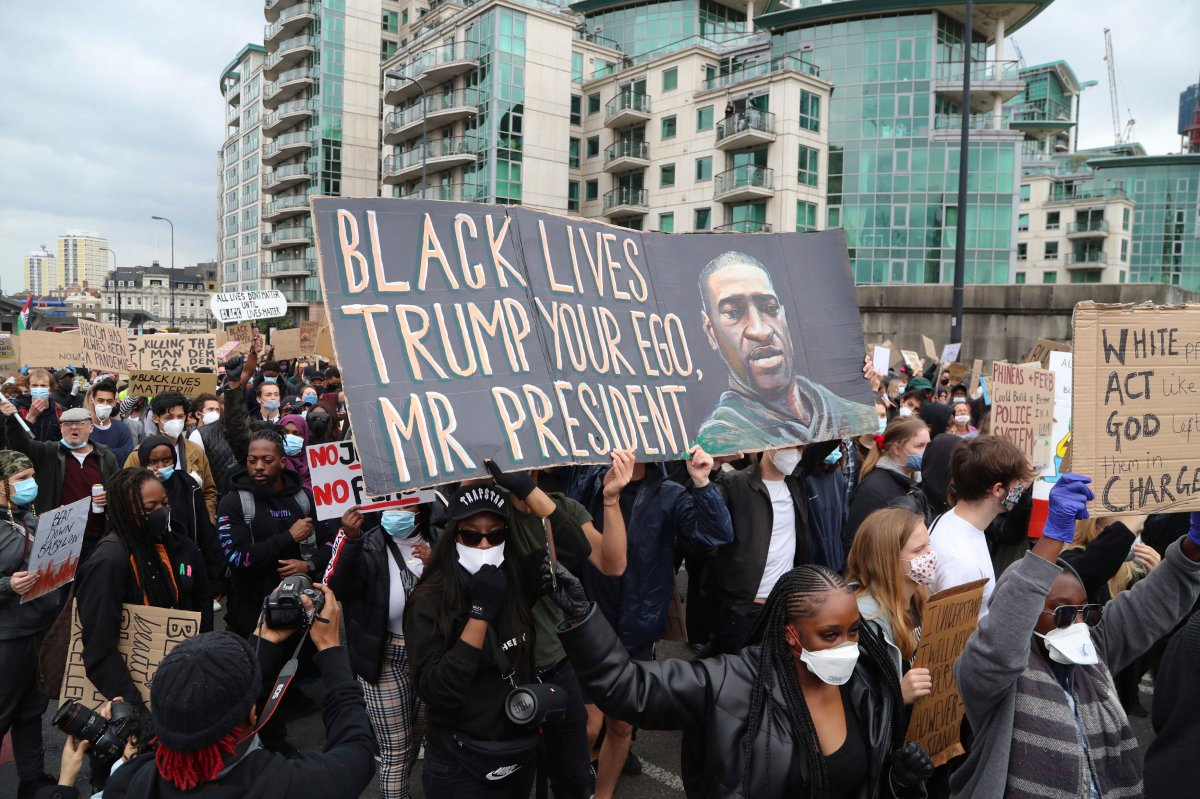 People take part in a Black Lives Matter protest rally outside the U.S. Embassy, in London, Sunday June 7, 2020, in response to the recent killing of George Floyd at the hands of police in Minneapolis that has led to protests in many countries and across the U.S.