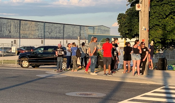 Residents gather outside of the Fearman's pork facility in Burlington Friday evening.