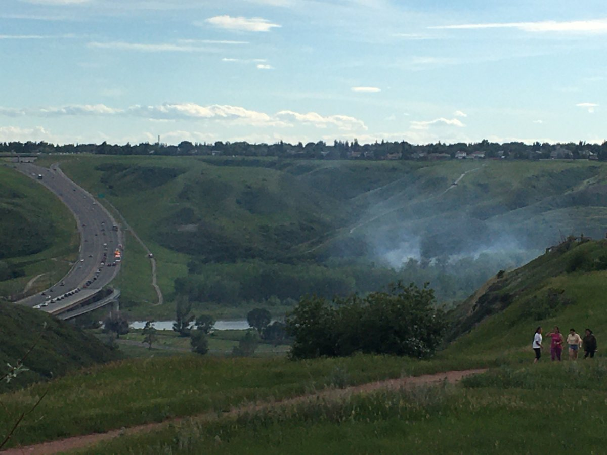 Smoke rises from a brush fire in the Oldman river valley in Lethbridge on June 22.