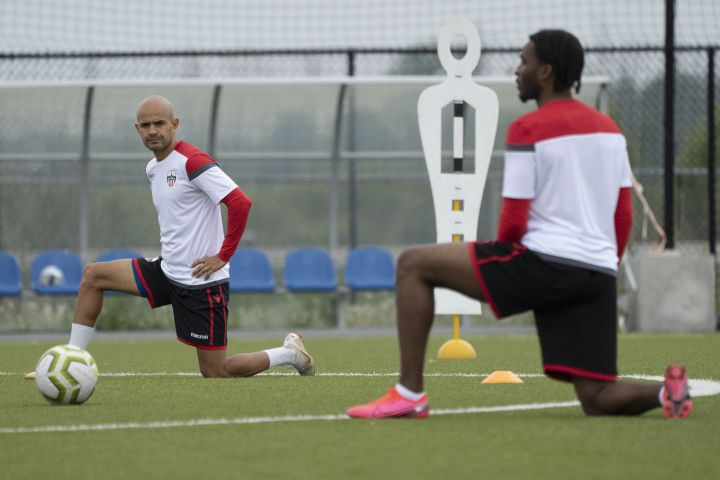 Atletico Ottawa midfielder Francisco Acuna and defender Vashon Neufville stretch during Atletico Ottawa's first team practice of their inaugural season in the Canadian Premier League (CPL) in Ottawa, Wednesday June 3, 2020.