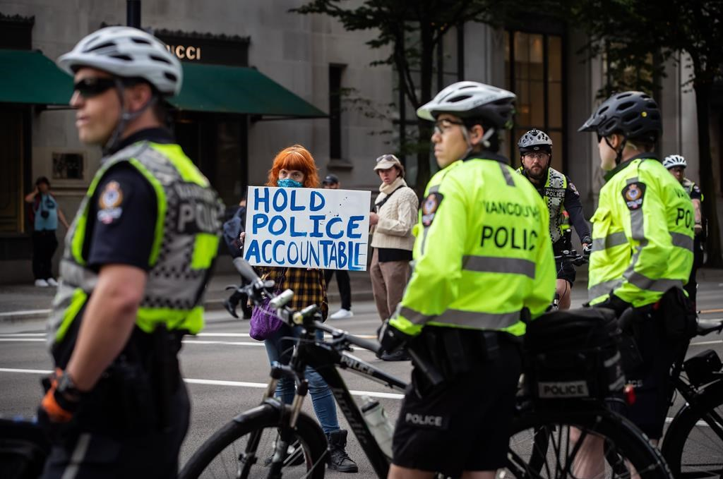 """A woman holds a sign reading """"Hold Police Accountable"""" near police officers watching as thousands of people gather for a peaceful demonstration in support of George Floyd and Regis Korchinski-Paquet and protest against racism, injustice and police brutality, in Vancouver, on Sunday, May 31, 2020."""