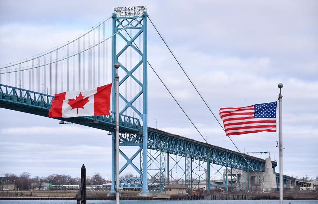 Canadian and American flags fly near the Ambassador Bridge at the Canada-USA border crossing in Windsor, Ont. on Saturday, March 21, 2020. THE CANADIAN PRESS/Rob Gurdebeke.