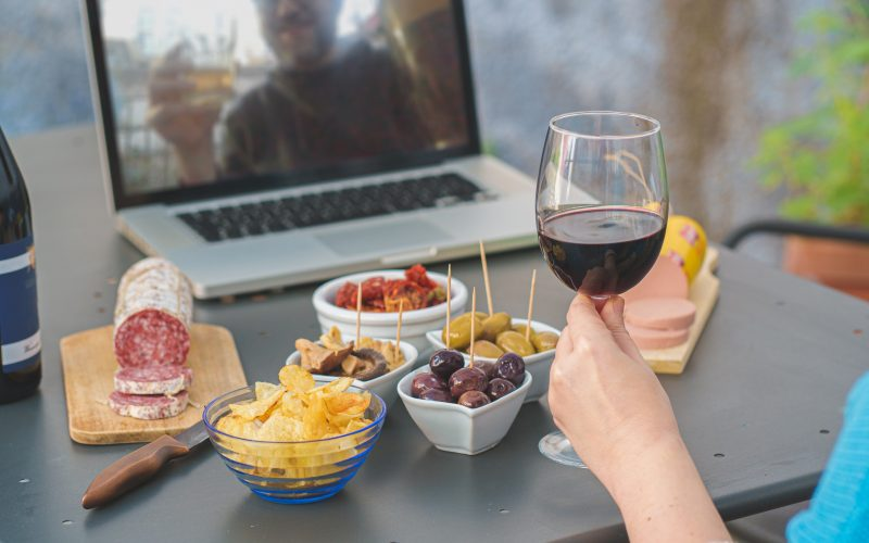 Two people share a drink and some snacks via a virtual meeting.
