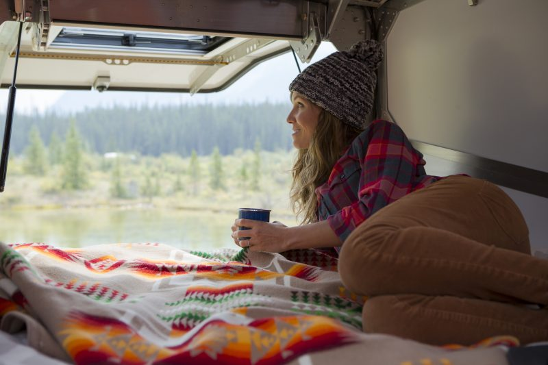 A woman relaxing in a trailer while camping in Jasper National Park.