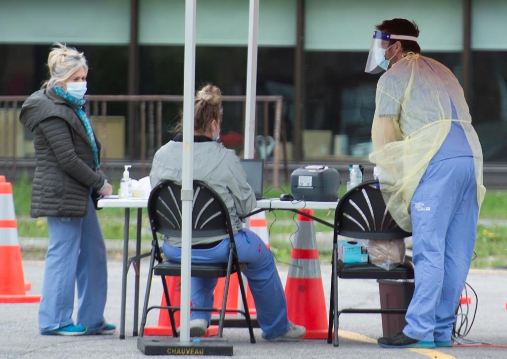 Health-care workers wait for people to tested at a COVID-19 mobile testing clinic in Montreal, Sunday, May 31, 2020, as the COVID-19 pandemic continues in Canada and around the world. THE CANADIAN PRESS/Graham Hughes.