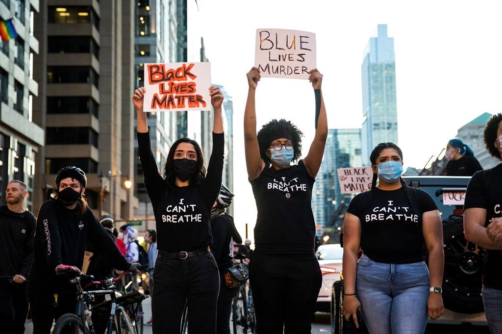 Protesters holds placards Saturday afternoon, May 30, 2020 in Chicago, I.L., as they join national outrage over the death of George Floyd, who died in police custody on Memorial Day in Minneapolis.