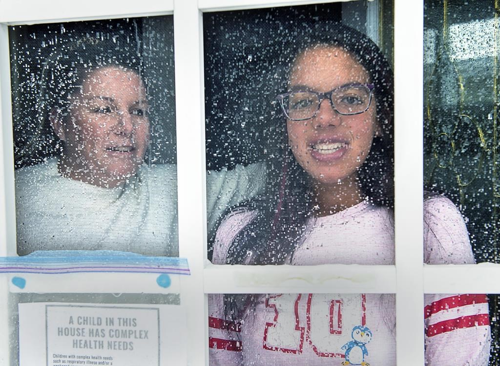 Lisa Ali and her 15-year-old daughter Tahlia look out from the front door of their Halifax-area home in Cole Harbour, N.S., on March 24, 2020.
