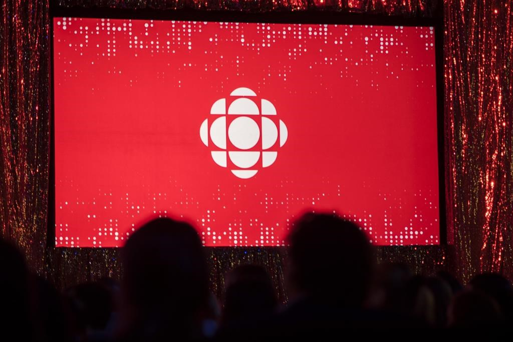 The CBC logo is projected onto a screen in Toronto on May 29, 2019. The CBC says it's accelerating efforts to meet diverse hiring, retention and promotion goals after its Yukon Morning radio show host lambasted the broadcaster for its failings live on-air. The public broadcaster says that by 2021–22, it wants half of all new hires for executive and senior management positions to be Indigenous people, visible minorities, or people with disabilities. It also plans to double retention and promotion rates for people from these three groups. THE CANADIAN PRESS/Tijana Martin.