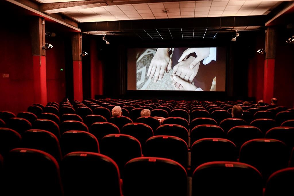 People sit in a cinema in Milan, Italy, Monday, June 15, 2020.