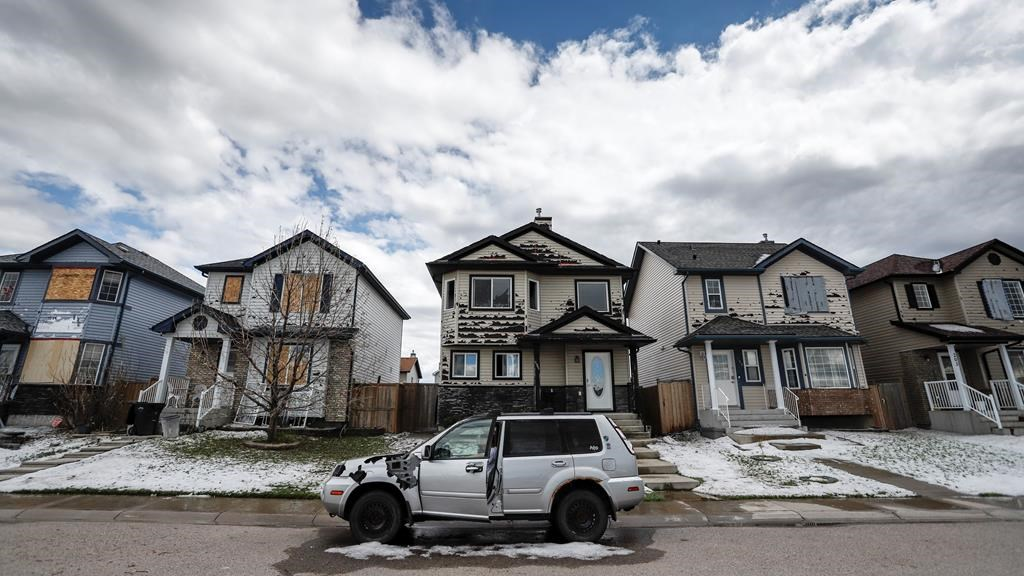 Residents survey the damage before begining cleanup in Calgary, Alta., Sunday, June 14, 2020, after a major hail storm damaged homes and flooded streets on Saturday.