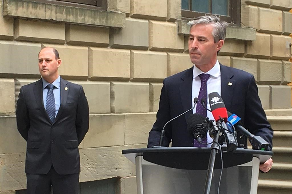 Nova Scotia Progressive Conservative Leader Tim Houston takes questions from reporters, Wednesday, June 24, 2020 outside the provincial legislature in Halifax as party education critic Tim Halman looks on. THE CANADIAN PRESS/Keith Doucette.
